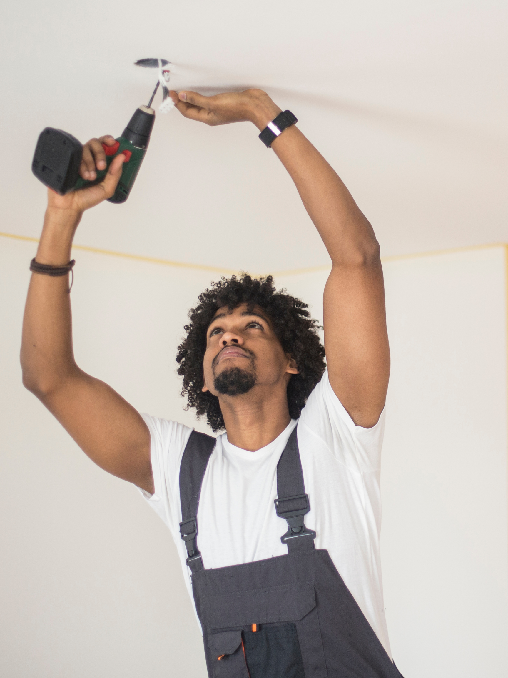 A man waring overalls and a white t-shirt using a drill to work on the electrical wiring in the ceiling